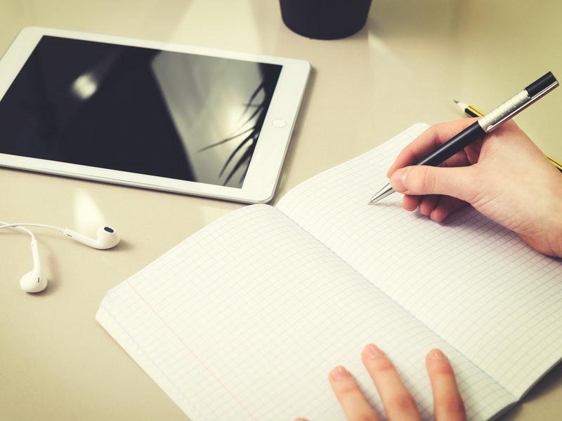 Estudiante trabajando con una tablet y un cuaderno