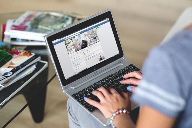 Mujer navegando por Facebook en un portátil