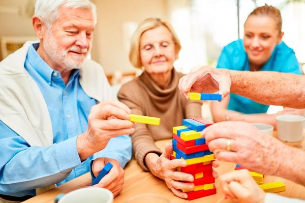 Mayores jugando a un juego de mesa en una residencia, junto a su cuidadora