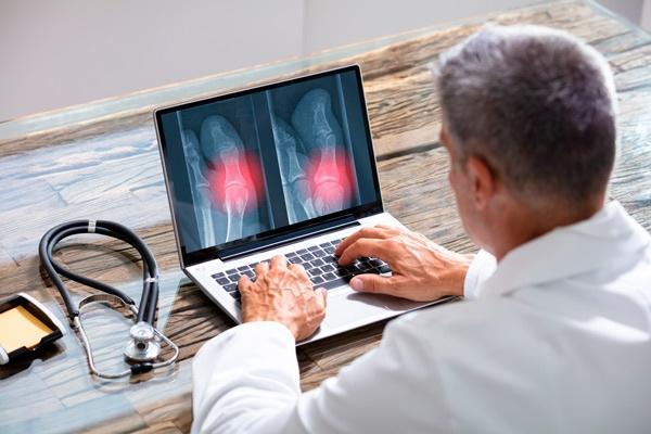 médico revisando radiografías digitales en portátil